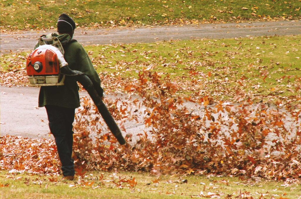 Man using leaf blower to demonstrate Leaf Removal & Gutter Cleaning services