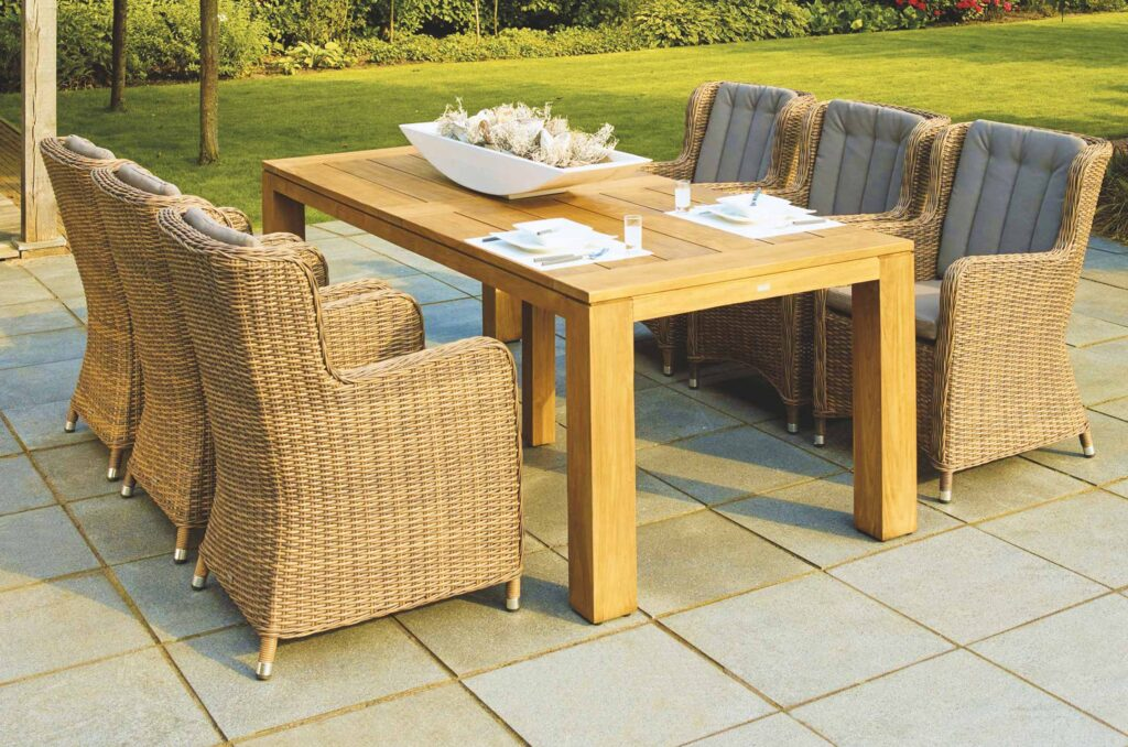 Nice outdoor dining table and chairs on a patio showcasing hardscaping services that include Paver Patios & Retaining Walls