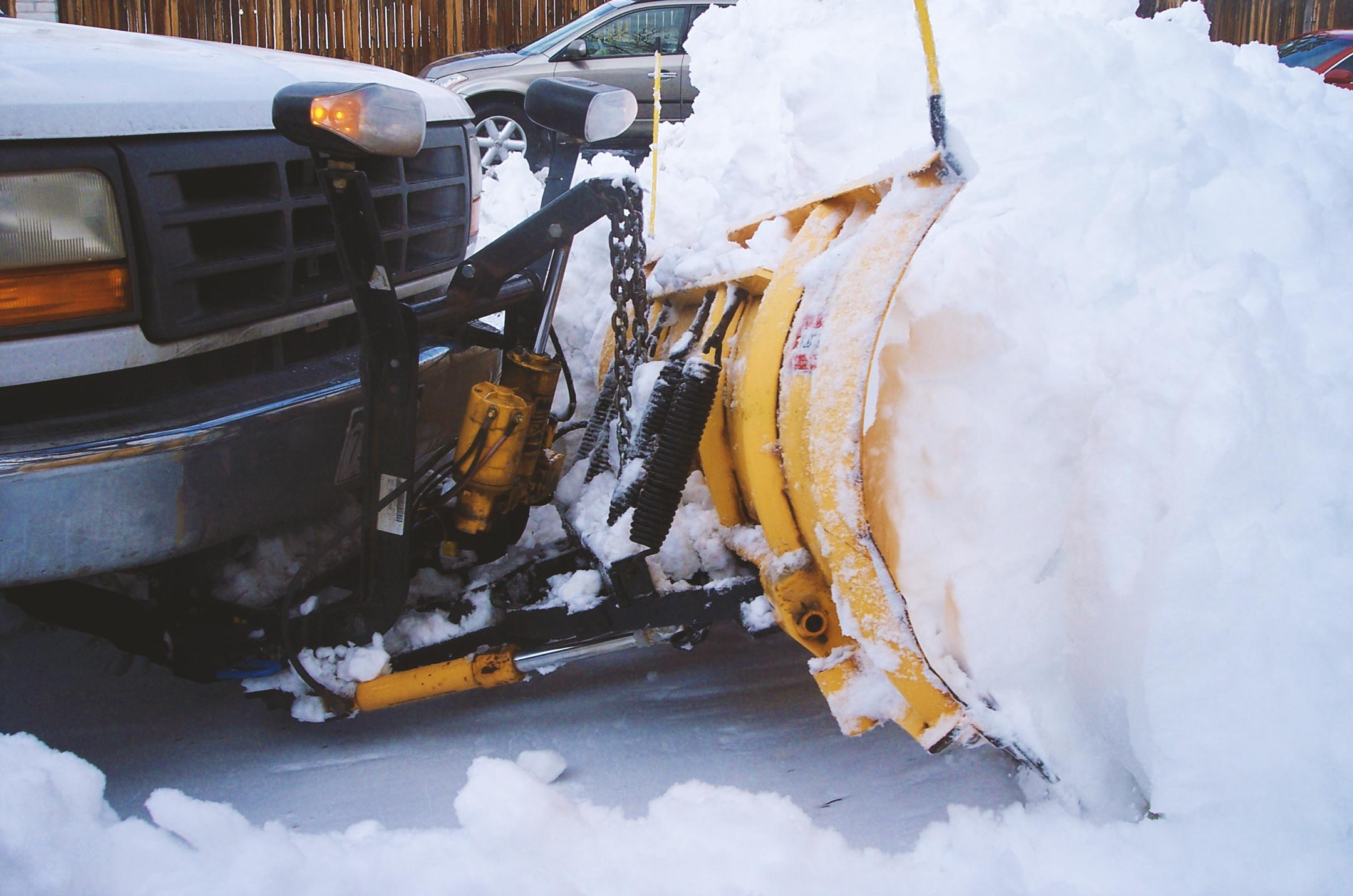 Close up of truck with snow plow attachment demonstrating Snow Removal with Plowing before Salting